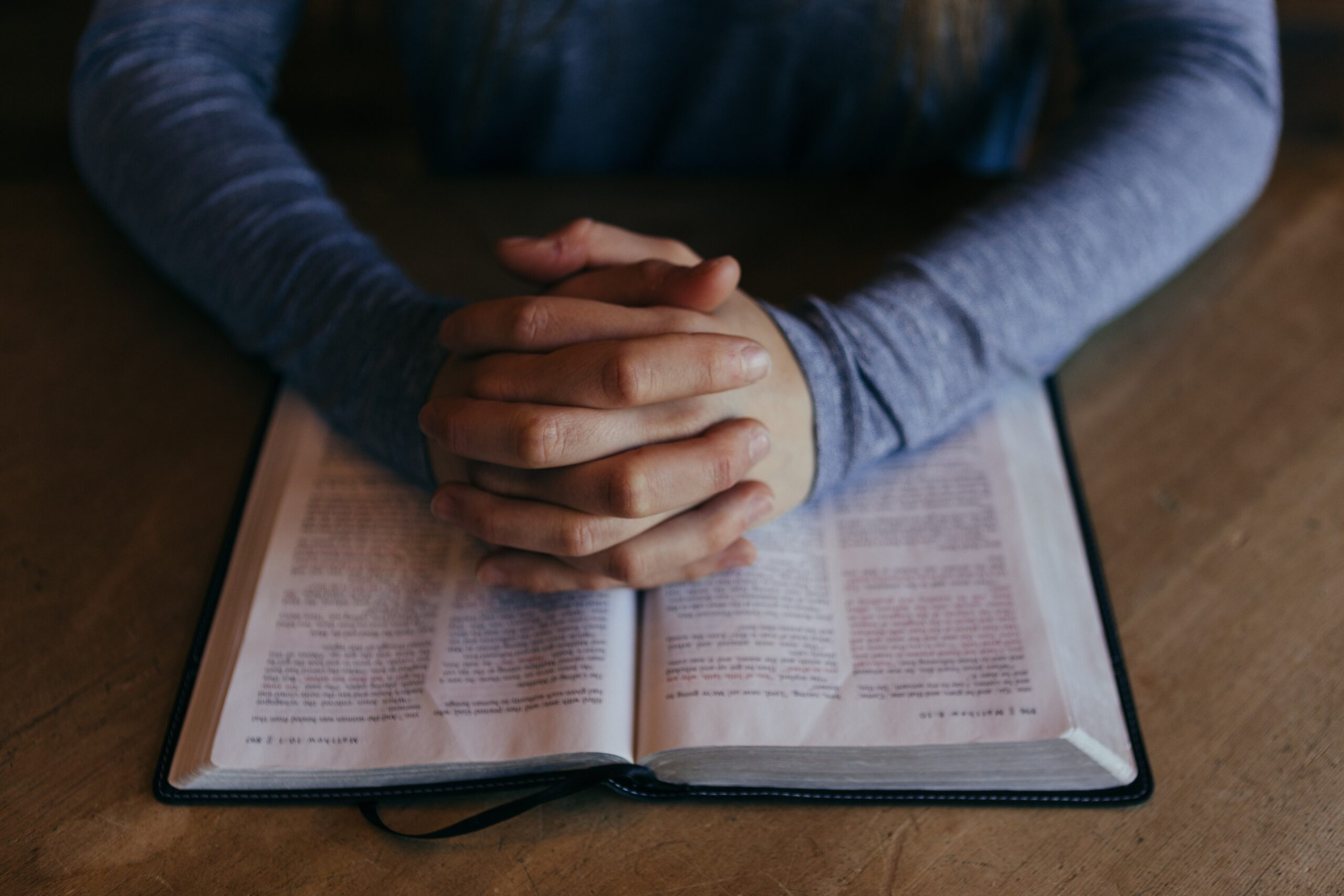Folded hands on bible taking for granted